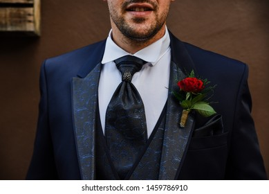 Detail of the boutonniere of a groom with a red rose