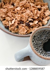 Detail of a breakfast meal combining a bowl of cereal and a mug of black coffee in matching stoneware set on a light color background.