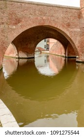 "detail of brick arches of ancient monumental ""Trepponti"" bridge, shot in bright light at Comacchio, Ferrara, Italy"
