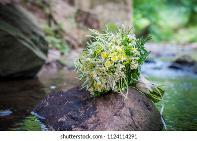Detail of bridal wedding bouquet. Closeup of bouquet on the rock in the river.