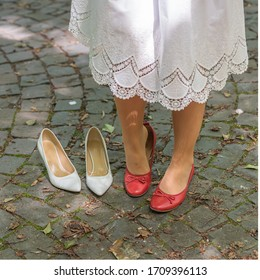 A detail of a bride changing shoes, dressed up in the wedding clothes outdoors in the park