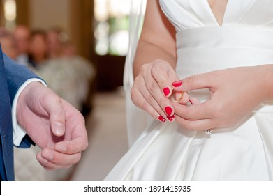 Detail of bride with red nail polish holding gold wedding band during exchanging of rings during wedding ceremony