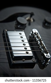 Detail of the bridge section of an electric guitar showing a humbucking pickup and adjustable bridge