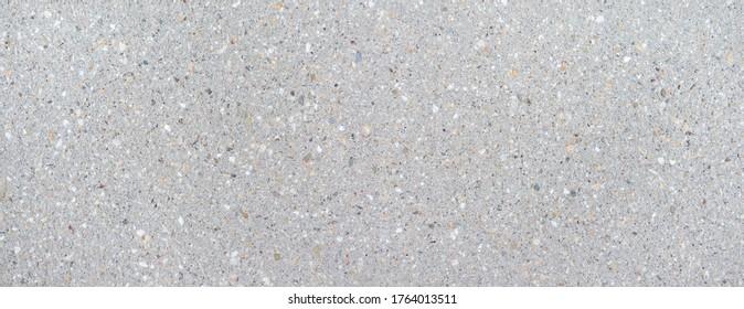 Detail einer hellen, grauen, glatten Betonplatte mit einem leichten Muster aus kleinen, farbigen Steinen