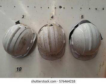 Detail broken white safety helmet on white board after work hard
