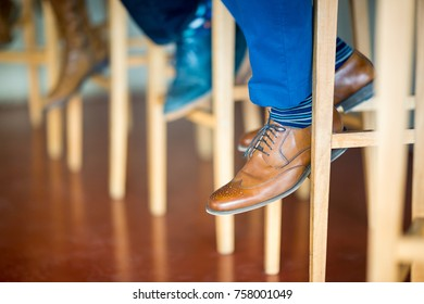 Detail of brown shoe of a gentleman sitting in the bar on a high stool