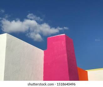 Detail of building facade in Scottsdale, Arizona, with hot pink and red paint against a dark blue sky