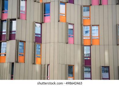 Detail of buildings facade, original colourfull windows. Orange, pink, red, blue windows. Diferent urban construction, arquitecture. Paris.