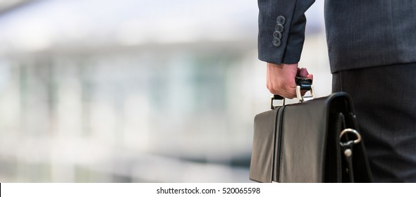 Detail of a businessman holding a leather briefcase. Wide image with large copy-space