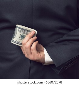 Detail of a businessman holding a stack of dollar banknotes behind his back