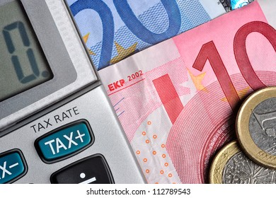 Detail of calculator, focusing the TAX key, next to some Euro bills and coins