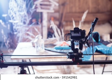 Detail of the camera on the slider and tripod in front of blurred colorful background with plants, bird feeder and wooden wall. Moment from shooting with blue color filter.