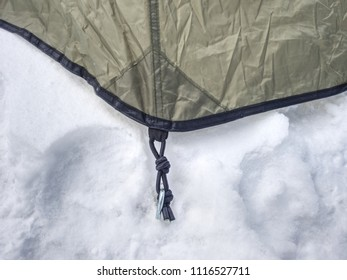 Detail of camping tent anchored in snow. Extreme winter trek. Aluminum Tent Poles and rainfly.