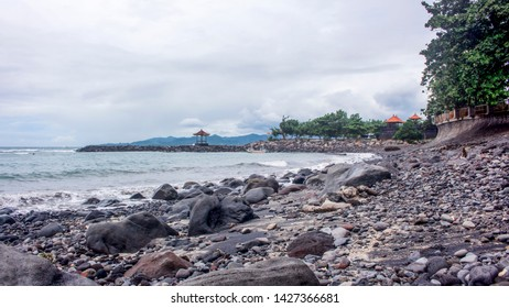 Detail of Candidasa stone beach in Bali during a cloudy day. Trees and traditional Balinese gazebo in the background