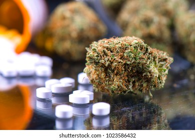 Detail of cannabis buds (chemo kush strain) and prescriptions pills over reflective surface - medical marijuana dispensary concept