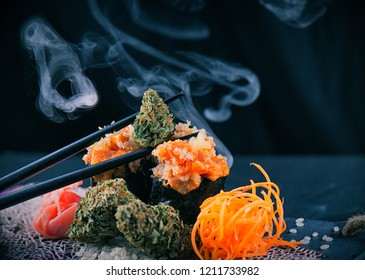 Detail of cannabis buds served on a sushi plate with smoke and chopsticks on a dark background, marijuana edibles concept