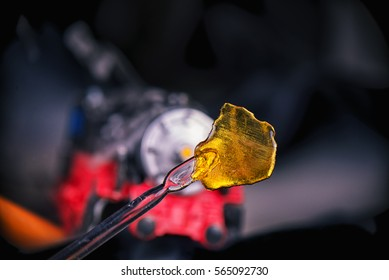 Detail of cannabis oil concentrate aka shatter (train wreck strain) with dabbing tool against dark background