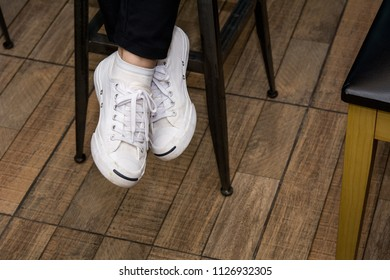 Detail of canvas shoes of a woman sitting cross legs on a high stool in cafe, Wooden floor background - Shutterstock ID 1126932305