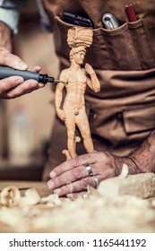 detail of carpenter making sculpture with electric drill