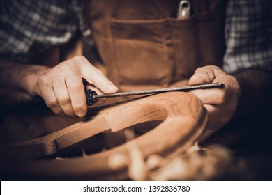Detail of a carpenter using a wooden rasp on a chair. inside his workshop.