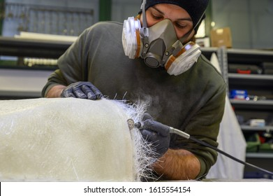 Detail of carpenter's hands filing the edge of a fiberglass part with a Dremel tool. Fiberglass processing: worker manually realizes a component in glass fiber.