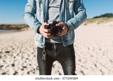 Detail of a casual young man photographer on the beach