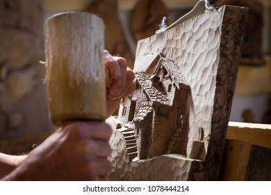Detail of caucasian middle aged scultor working on wood, natural daylight