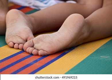Detail of a child feet on a sunbed.