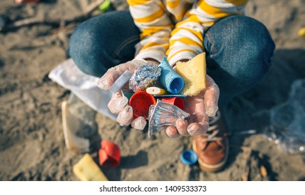 Detail of child hands with garbage collected from the beach