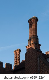 Detail of chimneys and parapet along the top of a Tudor building exterior wall with windows and ornaments