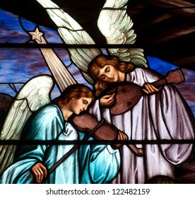 Detail of Christmas stained glass window depicting two angels playing musical instruments