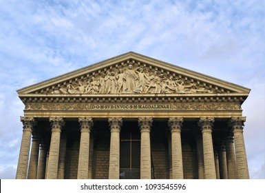 Detail of classic old architecture church St. Madeleine with columns against blue cloudy sky in Paris, France