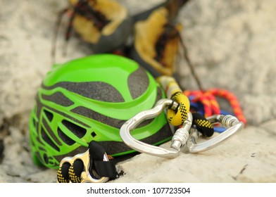 Detail of climbing helmet, carabiners and shoes lying on rock, focus on carabiner