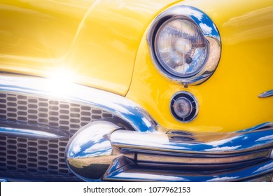 Detail close up of colorful yellow vintage car headlights