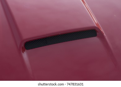 Detail close up of a red car chassis under full sunlight.