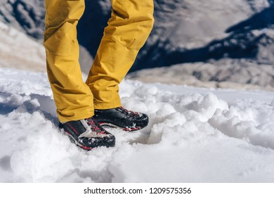 Detail close up shot of hiking or trekking shoes on snow. Technical outdoor boots on a glacier. Mountaineering or climbing winter shoes product photo.