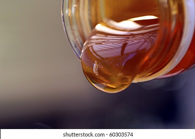 Detail close up of  stream of golden liquid Organic Honey pouring from jar