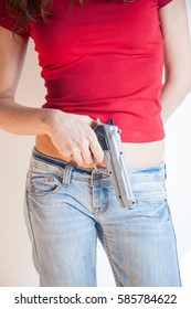 detail close up of woman with red tee shirt and blur jeans trousers with a plastic toy silver false pistol gun in her hand