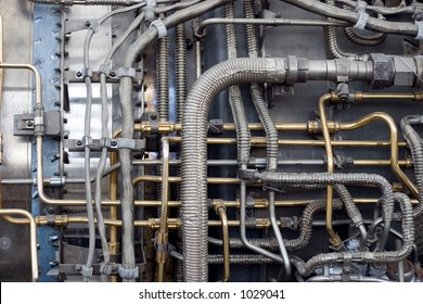 A detail closeup of a series of pipes in a jet engine with cables and connectors. Very technical and complicated.