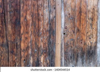 Detail closeup of weathered worn brown wood panel double doors to outhouse garage in traditional building in Chamonix France