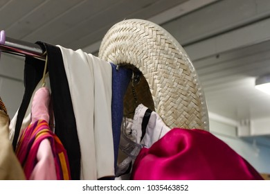 b6c33a61516 Detail closup of clothing rack of costumes backstage at the theater with straw  cowboy hat hanging