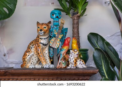 A detail of a collection of colourful statues in a city loft interior. A bohemian, modern, mix and match eclectic styled home with a wooden Mexican skeleton, a porcelain leopard, a parrot and plants