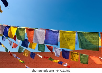 Detail of colorful buddhist praying flags on blue sky with roof