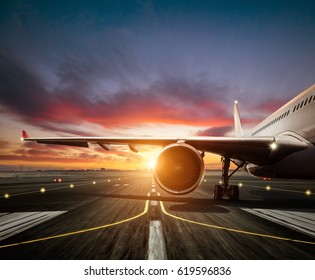 Detail of commercial airplane staying at the runway, wing and jet engine. Modern cityscape silhouettes on background