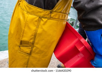 Detail of a commercial fisherman's traditional waterproof yellow oilskins. In St Ives, Cornwall, England.