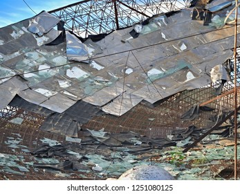Detail of a completely destroyed and broken old, very large satellite dish in the middle of a barren sand landscape in the south of Tenerife. The iron frame, aluminum and glass  is now visible.