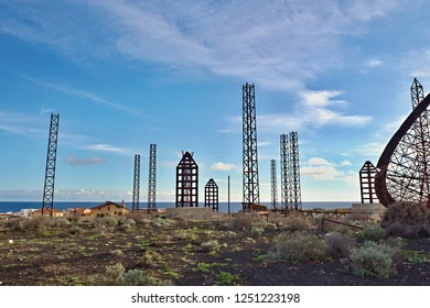 Detail of a completely destroyed and broken old, very large satellite dish in the middle of a barren sand landscape in the south of Tenerife. The iron frame is now visible.