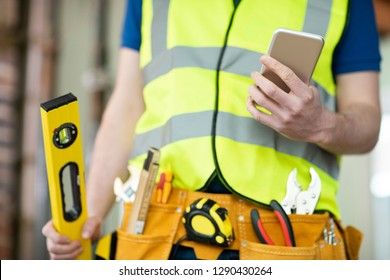 Detail Of Construction Worker On Building Site Wearing Tool Belt Using Mobile Phone