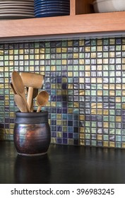 Detail of contemporary upscale home kitchen interior with iridescent glass tile backsplash wall and black concrete countertops. Wooden utensils are gathered in a raku pottery jug.