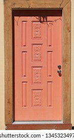 Detail of a coral colored door on a  brown building